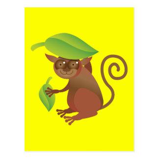 Tarsier hiding under a green leaf postcards