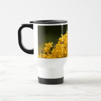 Taza amarilla minúscula del viaje de las flores