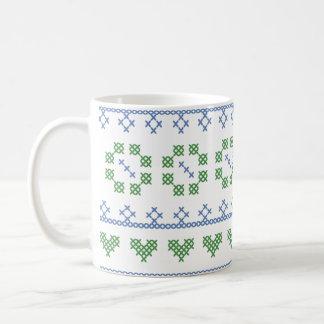 Taza azul y verde de la puntada de la cruz del