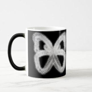 Taza blanca de la mariposa que aparece