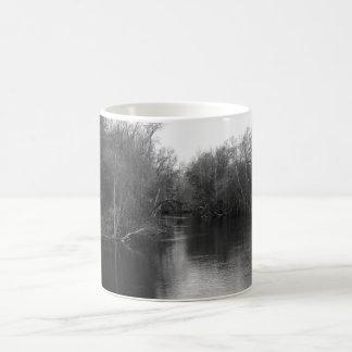 Taza blanco y negro de la escena del río de la