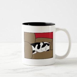 Taza blanco y negro del gato el dormir