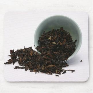 Taza con las hojas de té secas tapetes de ratón