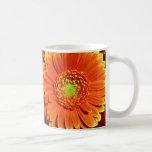 Taza de café anaranjada de la margarita del Gerber