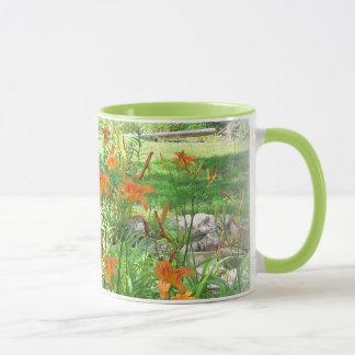 Taza de café anaranjada del jardín del lirio