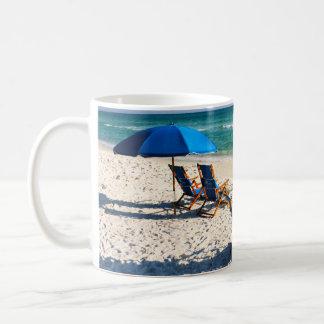 Taza de café azul de las sillas de playa de la