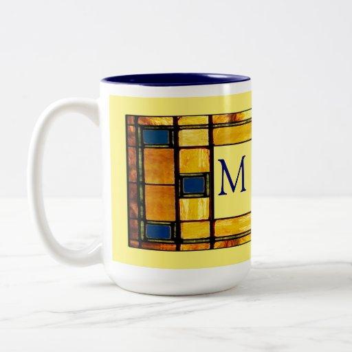 Taza de café azul y amarilla del monograma del vit