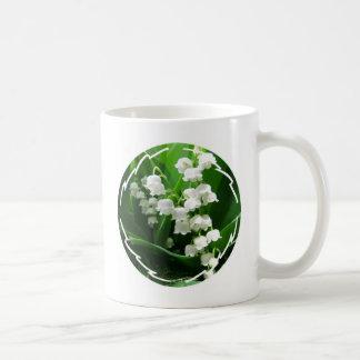 Taza de café blanca del lirio de los valles
