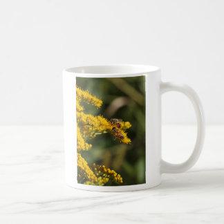 Taza de café de la foto de la vara de oro y de las