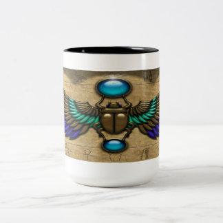 Taza de café de oro egipcia del escarabajo