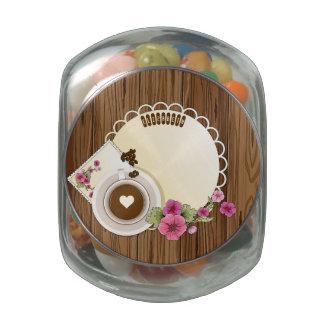 Taza de café en el tablero de madera con las frascos de cristal jelly belly