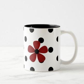 Taza de café negra y blanca del lunar con la flor