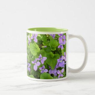 Taza de café - violetas de la hierba - reflejada