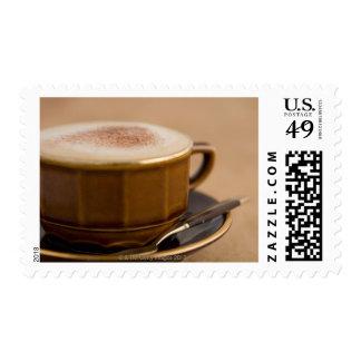 Taza de cappuccino con el polvo de cacao sellos