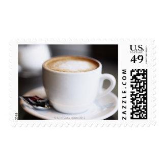 taza de latte del café en la tabla, primer timbres postales