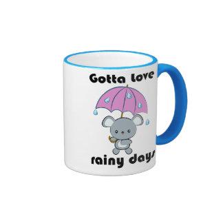 Taza de los días lluviosos del ratón y del paragua