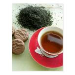 Taza de té negro con las galletas del chocolate postal