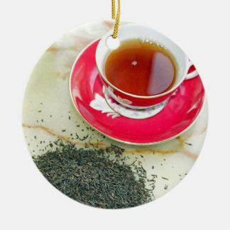 Taza de té negro con las hojas de té adorno navideño redondo de cerámica