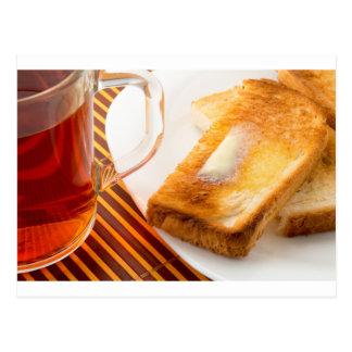 Taza de té y de tostada caliente con mantequilla postales