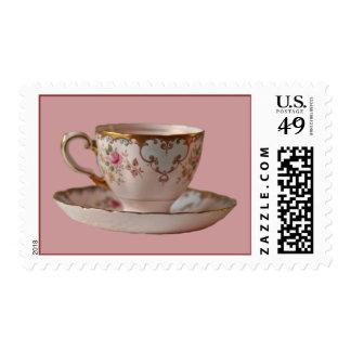 Taza de té y platillo rosados con los rosas sello postal