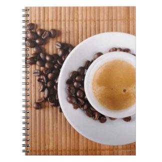 Taza del café express en una estera cuadernos