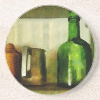 Taza del estaño y botella verde posavaso para bebida