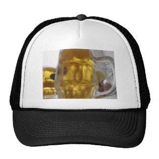 Taza fría de cerveza ligera en la tabla en un gorro de camionero