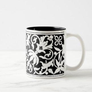 Taza negra y blanca del diseño floral