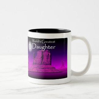Taza rosada de las manos cariñosas de la hija