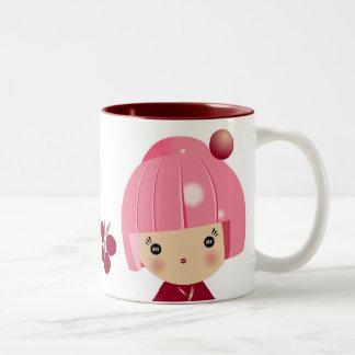 Taza rosada del trío de Kokeshi
