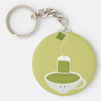 Taza sonriente de té verde con la bolsita de té llaveros