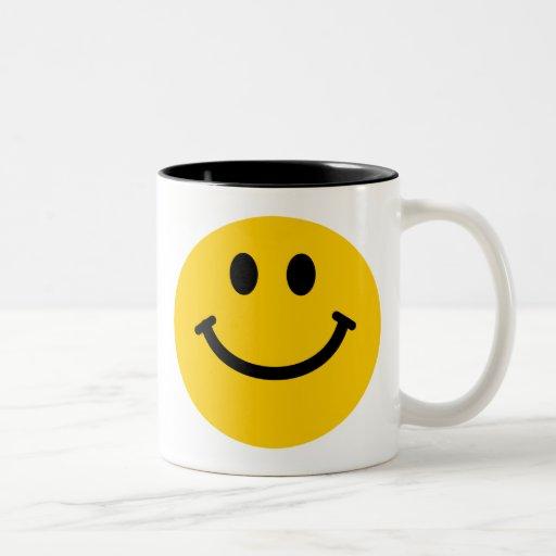 Taza sonriente feliz amarilla de la cara