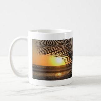 Taza tropical de la puesta del sol de la playa