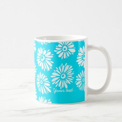 Taza verde de las flores azules claras