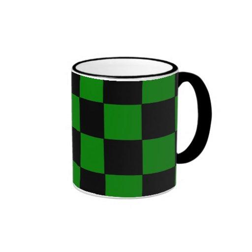 Taza verde y negra del tablero de damas