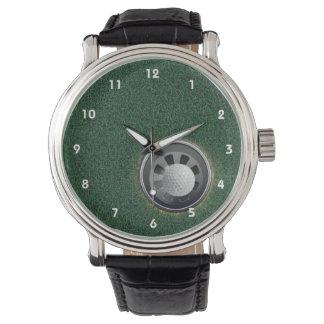 Taza y bola del golf en los verdes reloj
