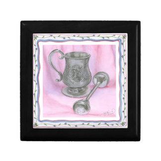 Taza y traqueteo de la herencia en fondo púrpura joyero cuadrado pequeño