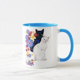 Tazas blancos y negros de los gatitos del jardín
