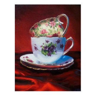 Tazas de té y postal roja del satén