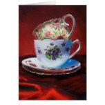Tazas de té y satén rojo tarjetón