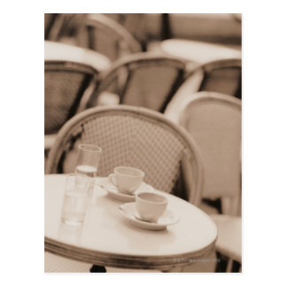 Tazas y vidrios de café en una tabla del café de postales