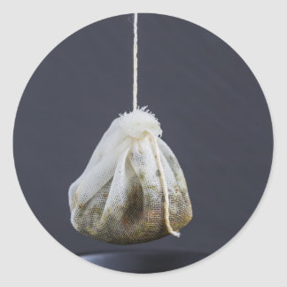 Tea bag is hung in a cup classic round sticker
