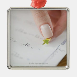 Teacher affixing gold star to math worksheet square metal christmas ornament