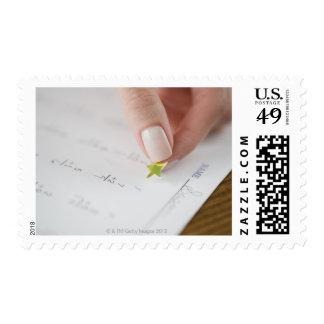 Teacher affixing gold star to math worksheet postage