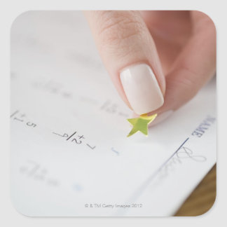Teacher affixing gold star to math worksheet square sticker
