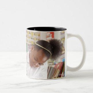 Teacher and school child working in classroom Two-Tone coffee mug