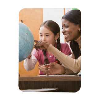 Teacher and student looking at globe magnet