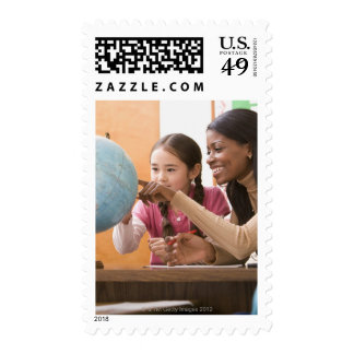 Teacher and student looking at globe postage stamps