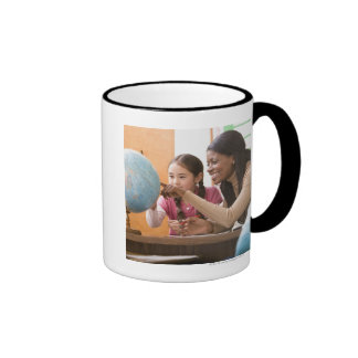 Teacher and student looking at globe ringer coffee mug