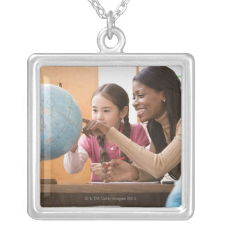 Teacher and student looking at globe square pendant necklace